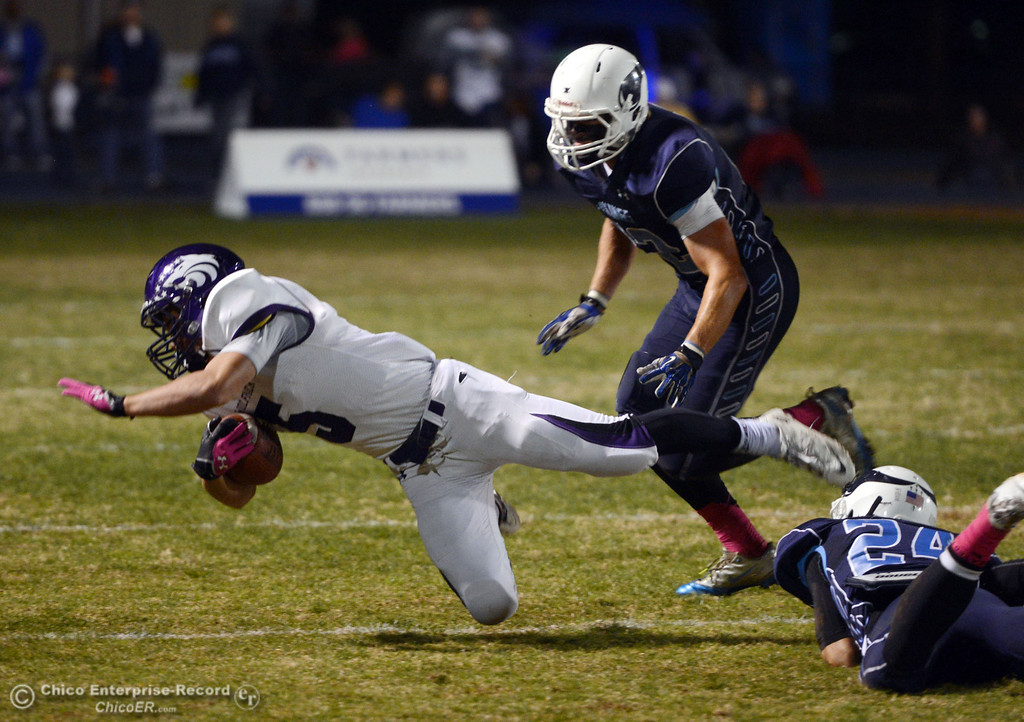 Description of . Shasta High\'s #5 Jake Callaway (left) is tackled by Pleasant Valley High\'s #24 Jack Soza (bottom) with #42 Chad Olsen (right) looking on  in the first quarter of their football game at PVHS Asgard Yard Friday, October 18, 2013 in Chico, Calif.  (Jason Halley/Chico Enterprise-Record)