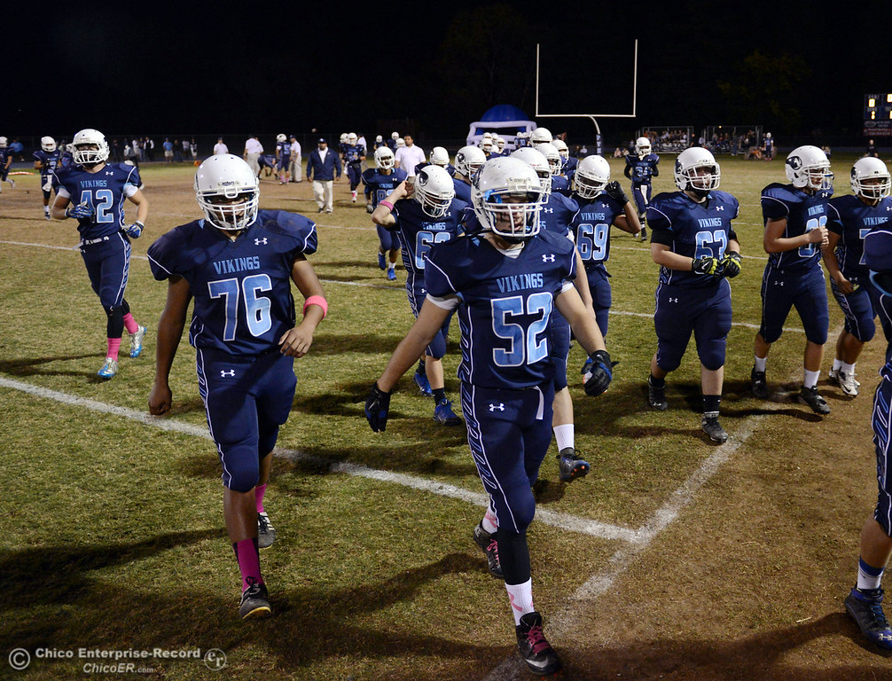 Description of . Pleasant Valley High\'s #76 Bailey Wasden (left) and #52 Cristian Miranda (right) take the field against Shasta High before the first quarter of their football game at PVHS Asgard Yard Friday, October 18, 2013 in Chico, Calif.  (Jason Halley/Chico Enterprise-Record)