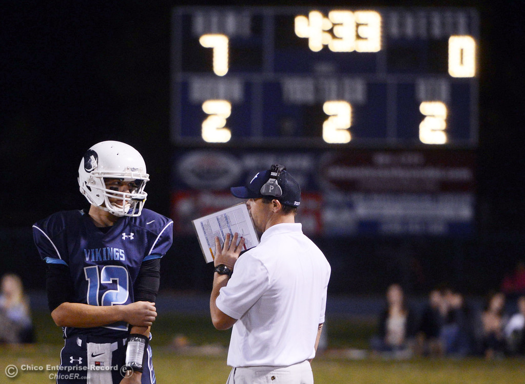 Description of . Pleasant Valley High\'s #12 Trent Darms (left) talks to coach Mark Cooley (right) against Shasta High in the second quarter of their football game at PVHS Asgard Yard Friday, October 18, 2013 in Chico, Calif.  (Jason Halley/Chico Enterprise-Record)
