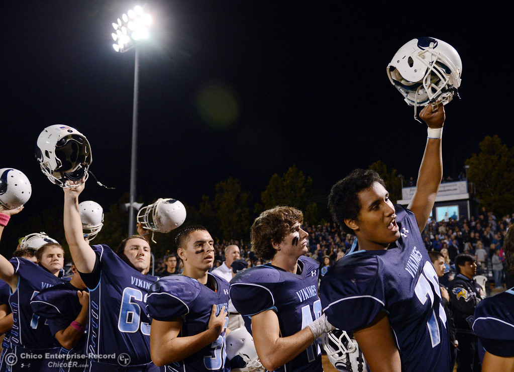 Description of . Pleasant Valley High\'s #63 Harrison Carter, #32 Jon Acevedo, #28 Logan O\'Sullivan, and #78 Alex Marquez (left to right) raise their helmets against Shasta High before the first quarter of their football game at PVHS Asgard Yard Friday, October 18, 2013 in Chico, Calif.  (Jason Halley/Chico Enterprise-Record)