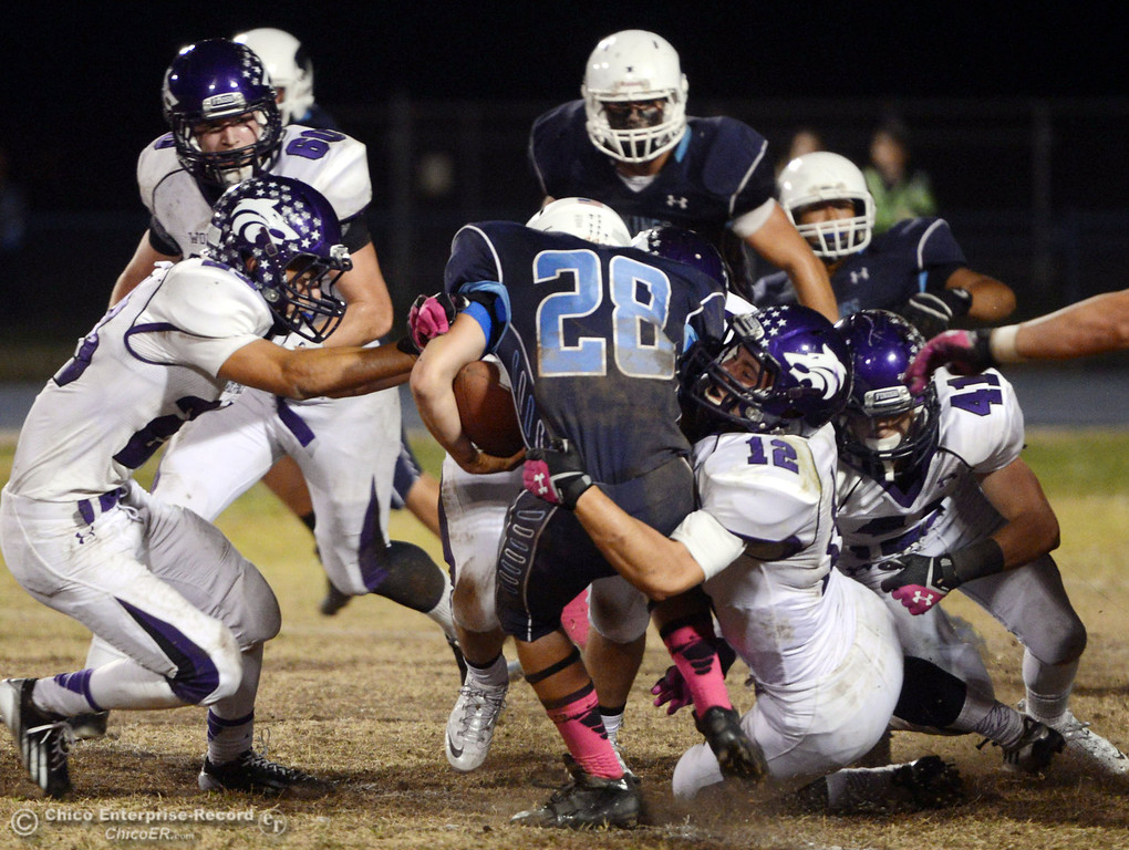Description of . Pleasant Valley Highs\' #28 Dylan Batie (center) is tackled against Shasta High\'s #12Colton Murrison (right) in the second quarter of their football game at PVHS Asgard Yard Friday, October 18, 2013 in Chico, Calif.  (Jason Halley/Chico Enterprise-Record)