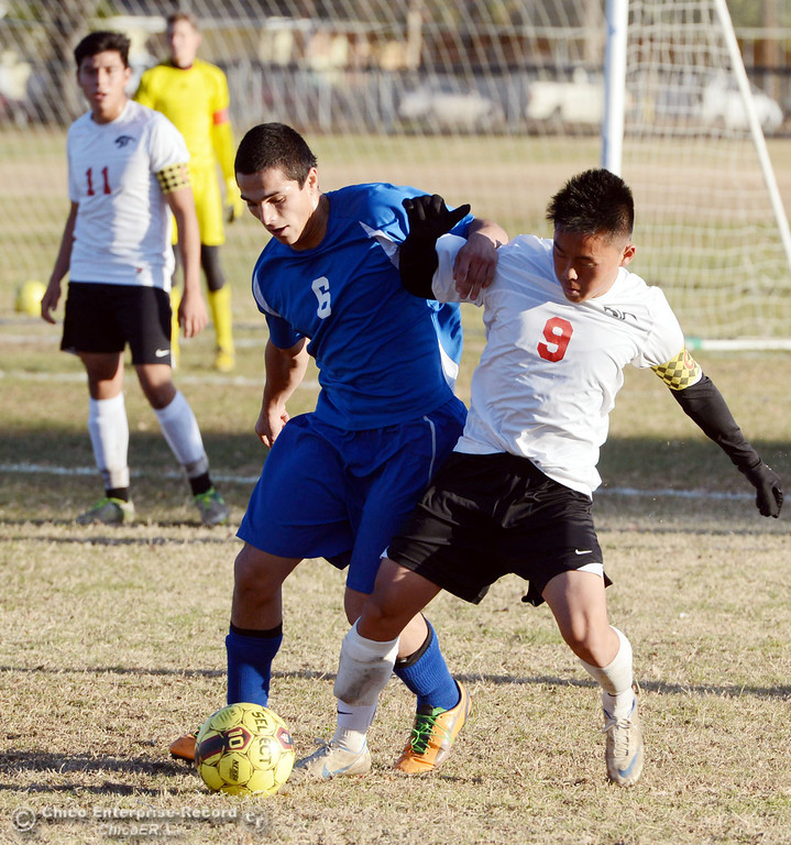 Description of . Chico High's #9 Rocky Xiong (right) battles against Orland High's #6 Hector Gutierrez (left) in the first half of their boys soccer game at CHS Thursday, December 19, 2013 in Chico, Calif. (Jason Halley/Chico Enterprise-Record)
