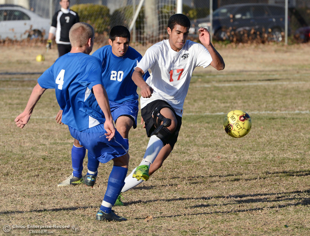 Description of . Chico High's #17 Omar Carey (right) battles against Orland High's #20 Jesse Gonzalez (center) as #4 Devin James (left) looks on in the first half of their boys soccer game at CHS Thursday, December 19, 2013 in Chico, Calif. (Jason Halley/Chico Enterprise-Record)