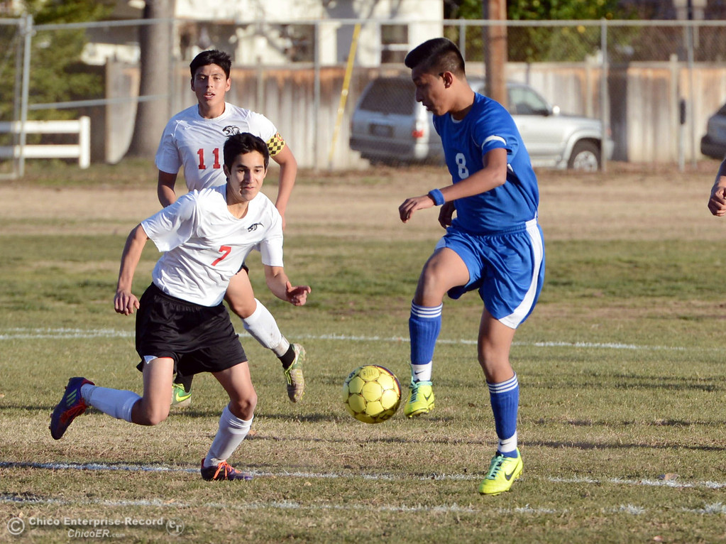 Description of . Chico High's #7 Claudio Quezada (left) battles against Orland High's #8 Israel Zintzun (right) in the first half of their boys soccer game at CHS Thursday, December 19, 2013 in Chico, Calif. (Jason Halley/Chico Enterprise-Record)