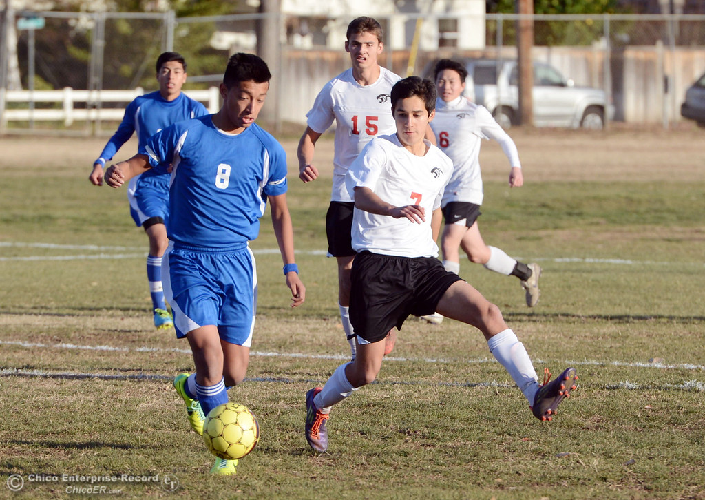 Description of . Orland High's #8 Israel Zintzun (left) against Chico High's #7 Claudio Quezada (right) in the first half of their boys soccer game at CHS Thursday, December 19, 2013 in Chico, Calif. (Jason Halley/Chico Enterprise-Record)