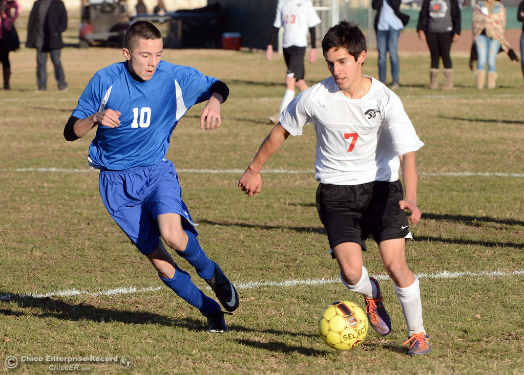 Description of . Chico High's #7 Claudio Quezada (right) battles against Orland High's #10 Marcos Martinez (left) in the first half of their boys soccer game at CHS Thursday, December 19, 2013 in Chico, Calif. (Jason Halley/Chico Enterprise-Record)