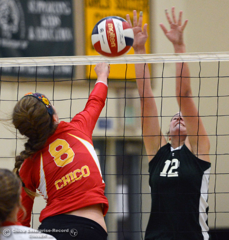 Description of . Chico High's #8 Emma Contreras (left) spikes against Paradise High's #12 Mariah Mundt (right) in the first game of their girls volleyball match at PHS Thursday, October 10, 2013 in Paradise, Calif.  (Jason Halley/Chico Enterprise-Record)