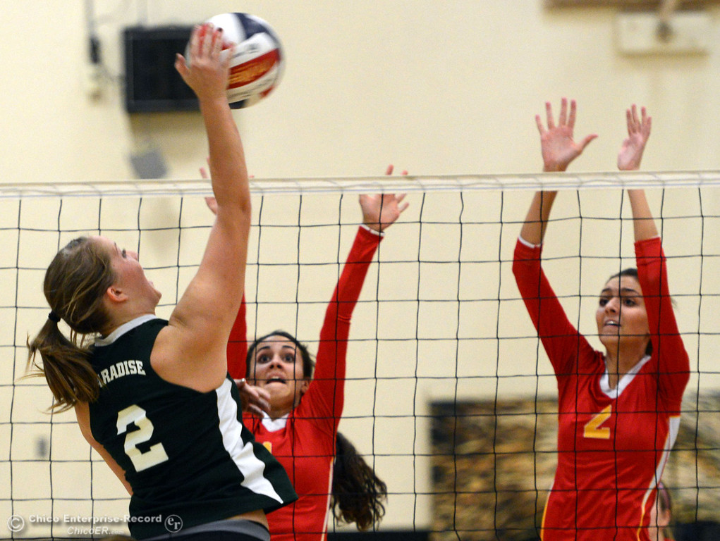 Description of . Paradise High's #2 Bailey Bengson (left) spikes the ball against Chico High's #1 Cia Seibert (center) and #2 Sydney Gaskey (right) in the second game of their girls volleyball match at PHS Thursday, October 10, 2013 in Paradise, Calif.  (Jason Halley/Chico Enterprise-Record)