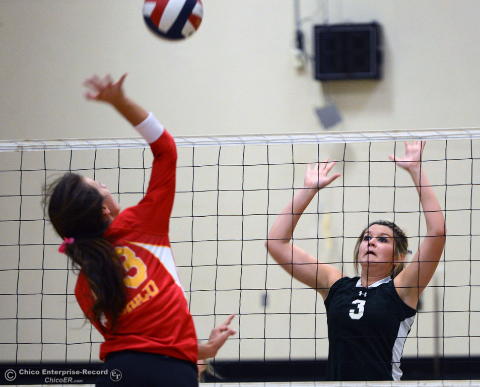 Description of . Chico High\'s #13 Becca Korte (left) spikes against Paradise High\'s #3 Kelsi Earhart (right) in the first game of their girls volleyball match at PHS Thursday, October 10, 2013 in Paradise, Calif.  (Jason Halley/Chico Enterprise-Record)