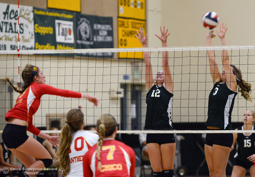 Description of . Chico High's #8 Emma Contreras (left) spikes against Paradise High's #12 Mariah Mundt (center) and #3 Kelsi Earhart (right) in the first game of their girls volleyball match at PHS Thursday, October 10, 2013 in Paradise, Calif.  (Jason Halley/Chico Enterprise-Record)