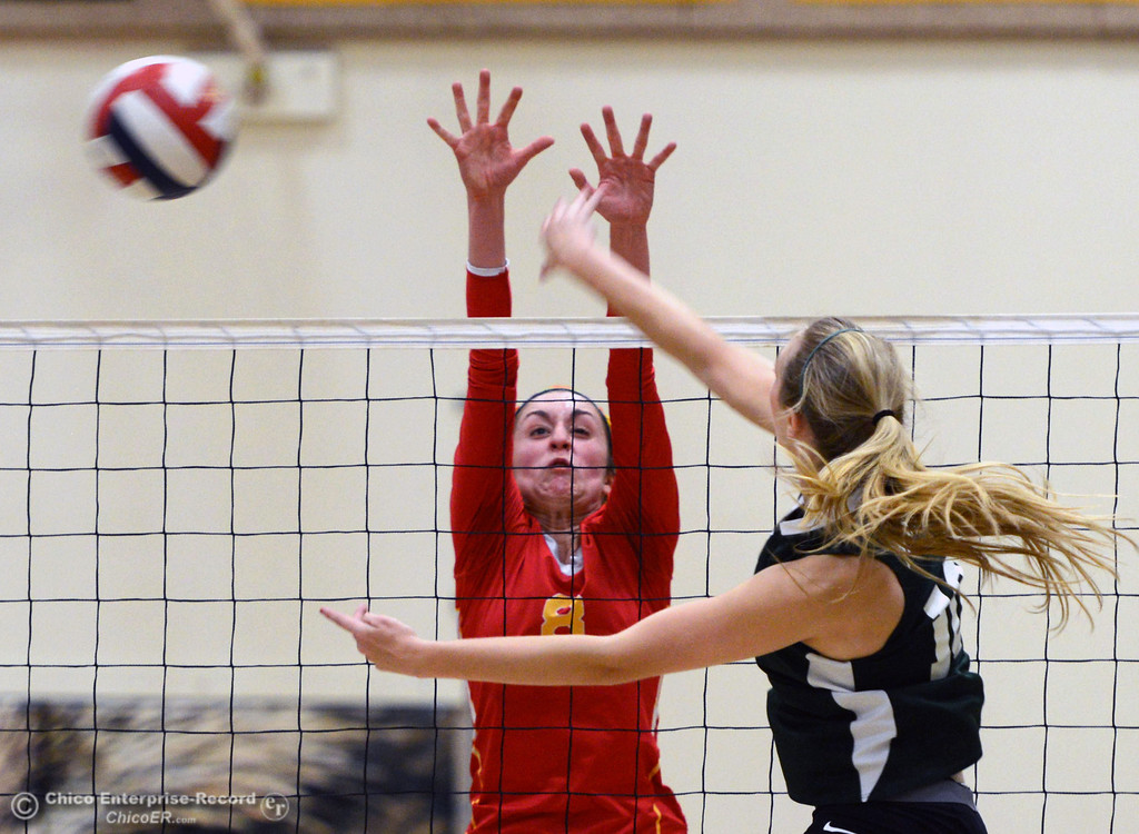 Description of . Chico High's #8 Emma Contreras (left) is unable to block against Paradise High's #10 Larissa Knifong (right) in the second game of their girls volleyball match at PHS Thursday, October 10, 2013 in Paradise, Calif.  (Jason Halley/Chico Enterprise-Record)