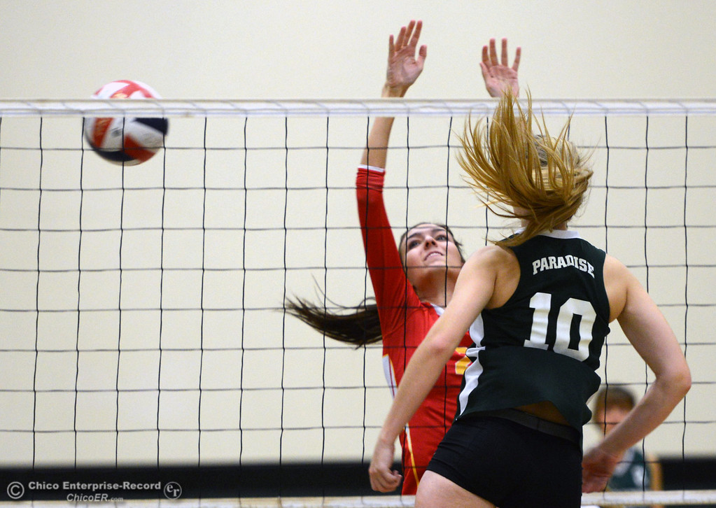 Description of . Paradise High's #10 Larissa Knifong (right) spikes against Chico High's #2 Sydney Gaskey (left) in the first game of their girls volleyball match at PHS Thursday, October 10, 2013 in Paradise, Calif.  (Jason Halley/Chico Enterprise-Record)