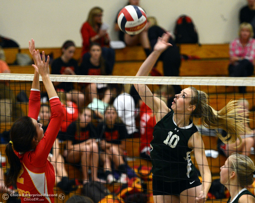 Description of . Paradise High's #10 Larissa Knifong (right) spikes the ball against Chico High's #2 Sydney Gaskey (left) in the second game of their girls volleyball match at PHS Thursday, October 10, 2013 in Paradise, Calif.  (Jason Halley/Chico Enterprise-Record)