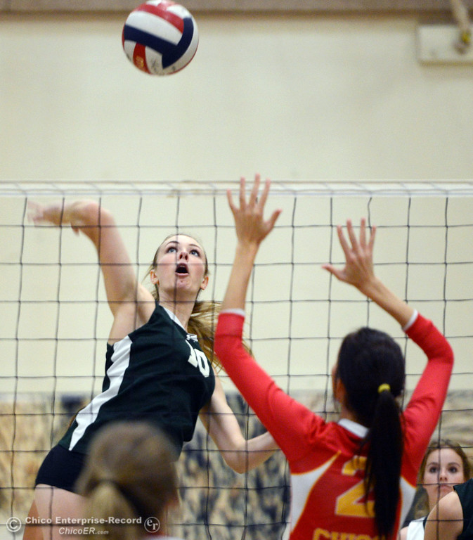 Description of . Paradise High\'s #10 Larissa Knifong (left) spikes against Chico High\'s #2 Sydney Gaskey (right) in the first game of their girls volleyball match at PHS Thursday, October 10, 2013 in Paradise, Calif.  (Jason Halley/Chico Enterprise-Record)