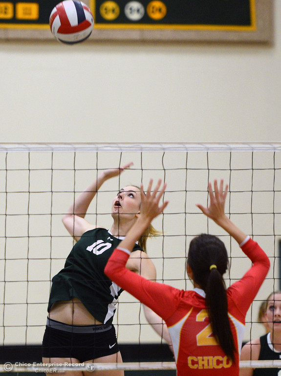 Description of . Paradise High's #10 Larissa Knifong (left) spikes against Chico High's #2 Sydney Gaskey (right) in the first game of their girls volleyball match at PHS Thursday, October 10, 2013 in Paradise, Calif.  (Jason Halley/Chico Enterprise-Record)