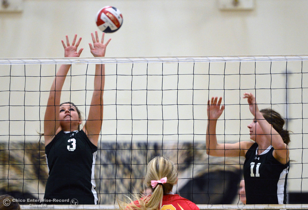 Description of . Chico High's #13 Becca Korte (center) spikes against Paradise High's #3 Kelsi Earhart (left) and #11 Jennifer Olson (right) in the first game of their girls volleyball match at PHS Thursday, October 10, 2013 in Paradise, Calif.  (Jason Halley/Chico Enterprise-Record)