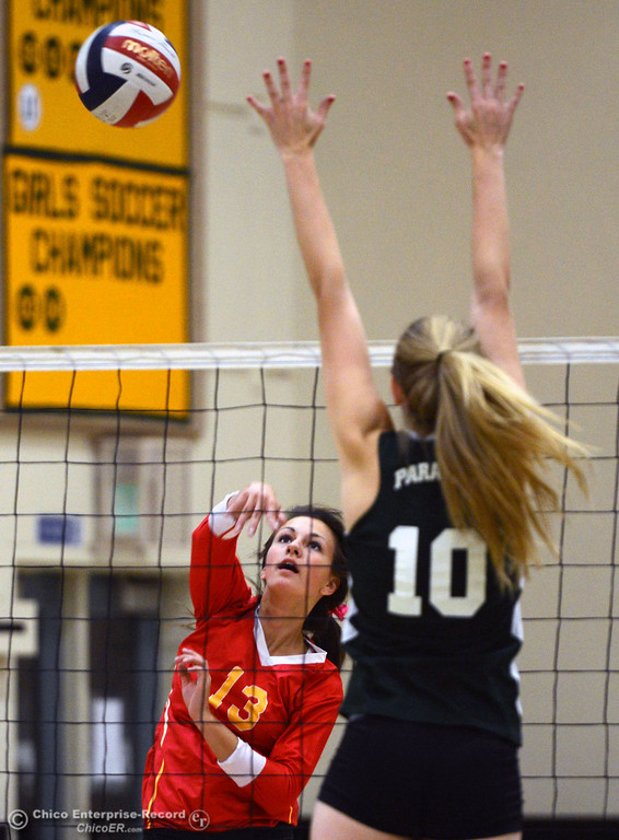 Description of . Chico High's #13 Becca Korte (left) spikes against Paradise High's #10 Larissa Knifong (right) in the second game of their girls volleyball match at PHS Thursday, October 10, 2013 in Paradise, Calif.  (Jason Halley/Chico Enterprise-Record)