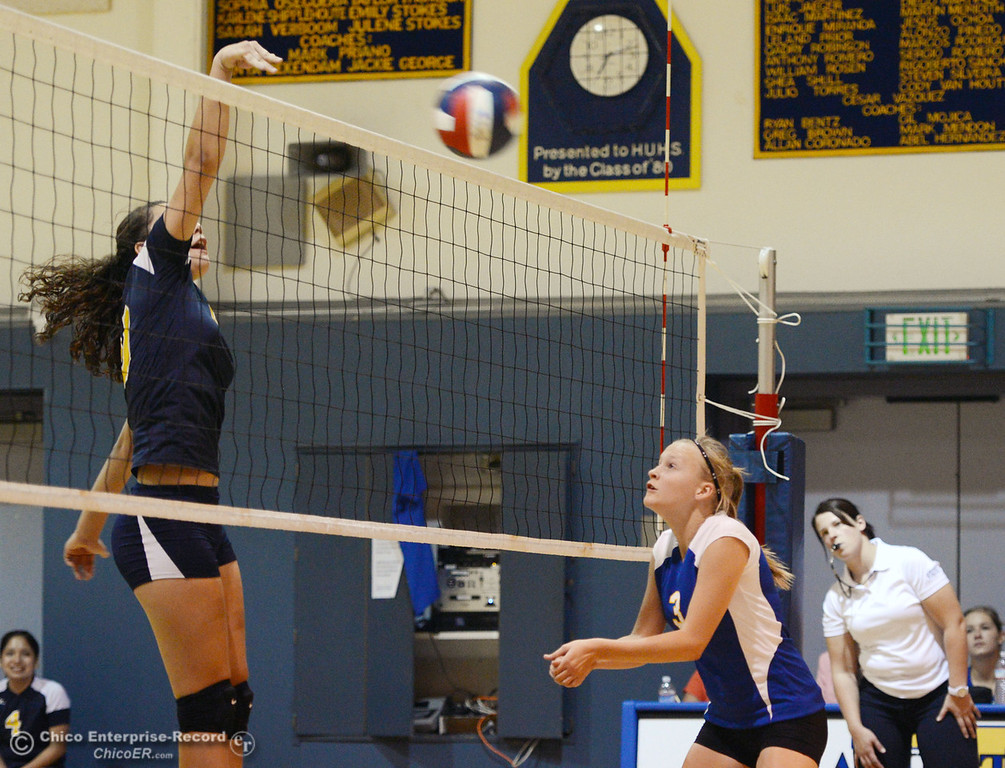 Description of . Hamilton High's #3 Kendra Gordon (right) watches against Gridley High's #20 Haylee Coats (left) who spikes the ball in their second game of their volleyball match Thursday, August 29, 2013 in Chico, Calif.  (Jason Halley/Chico Enterprise-Record)