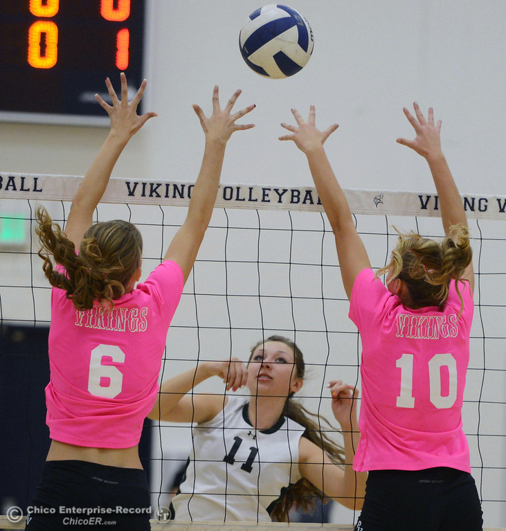 "Description of . Pleasant Valley High\'s #6 Hanne Henriksen (left) and #10 Ashley Geiger (right) attempt to block against Paradise High\'s #11 Jennifer Olson (center) in the second game of their volleyball match at PVHS Varley Gym Thursday, October 17, 2013 in Chico, Calif. PV volleyball wore pink instead of blue vs Paradise at ""Fight Like a Viking Night,\"" to raise money for cancer research. (Jason Halley/Chico Enterprise-Record)"