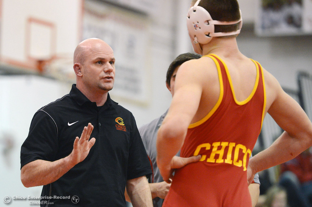Description of . Chico High's coach Keith Rollins (left) talks to Nicholas Maximov (right) who wrestles against Orland High's Omar Ortega in the 182 lbs wrestling match at CHS Wednesday, December 18, 2013 in Chico, Calif. (Jason Halley/Chico Enterprise-Record)