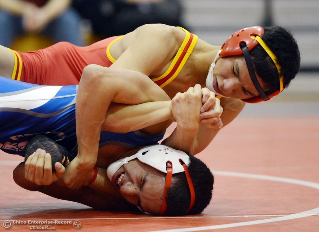 Description of . Chico High's Morgan Sauseda (top) wrestles against Orland High's Hugo Punzo (bottom) in the 113 lbs wrestling match at CHS Wednesday, December 18, 2013 in Chico, Calif. (Jason Halley/Chico Enterprise-Record)
