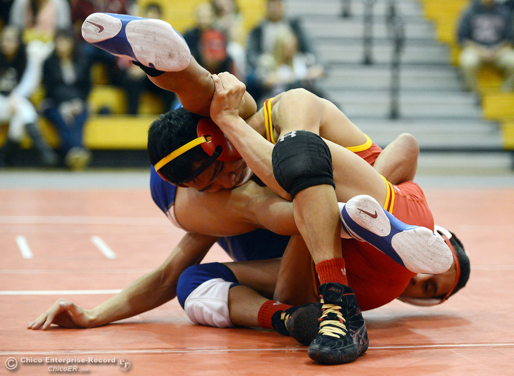 Description of . Chico High\'s Morgan Sauseda (front) wrestles against Orland High\'s Hugo Punzo (back) in the 113 lbs wrestling match at CHS Wednesday, December 18, 2013 in Chico, Calif. (Jason Halley/Chico Enterprise-Record)