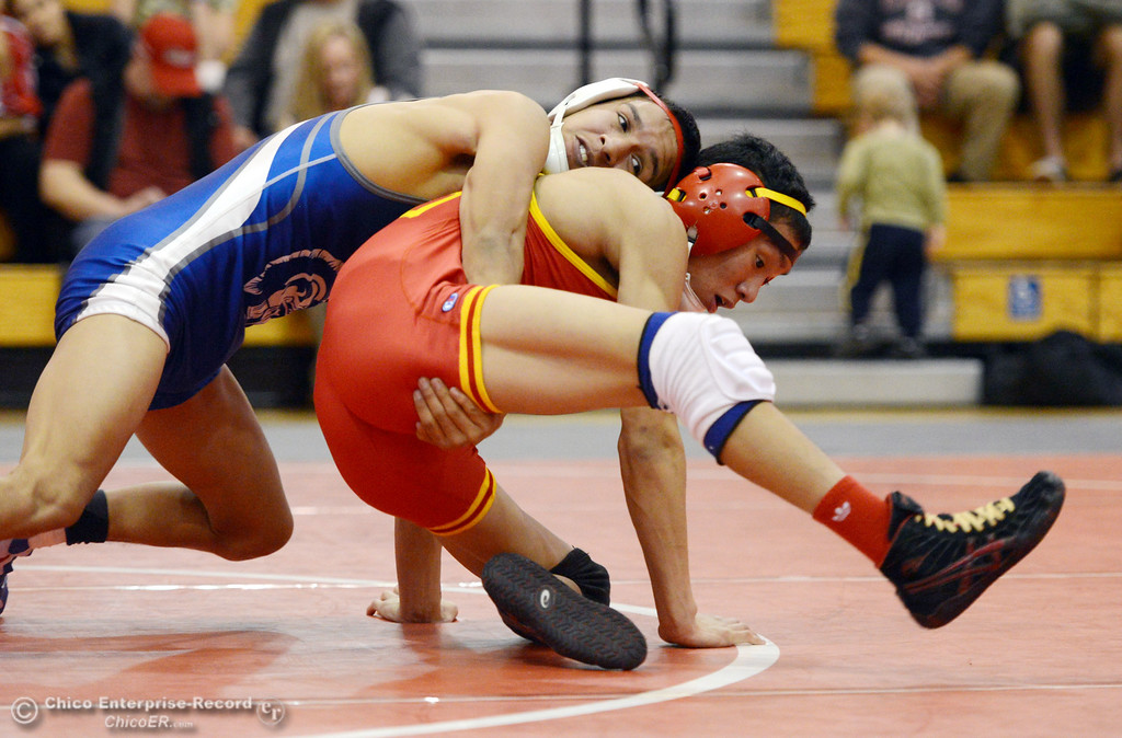 Description of . Chico High\'s Morgan Sauseda (right) wrestles against Orland High\'s Hugo Punzo (left) in the 113 lbs wrestling match at CHS Wednesday, December 18, 2013 in Chico, Calif. (Jason Halley/Chico Enterprise-Record)