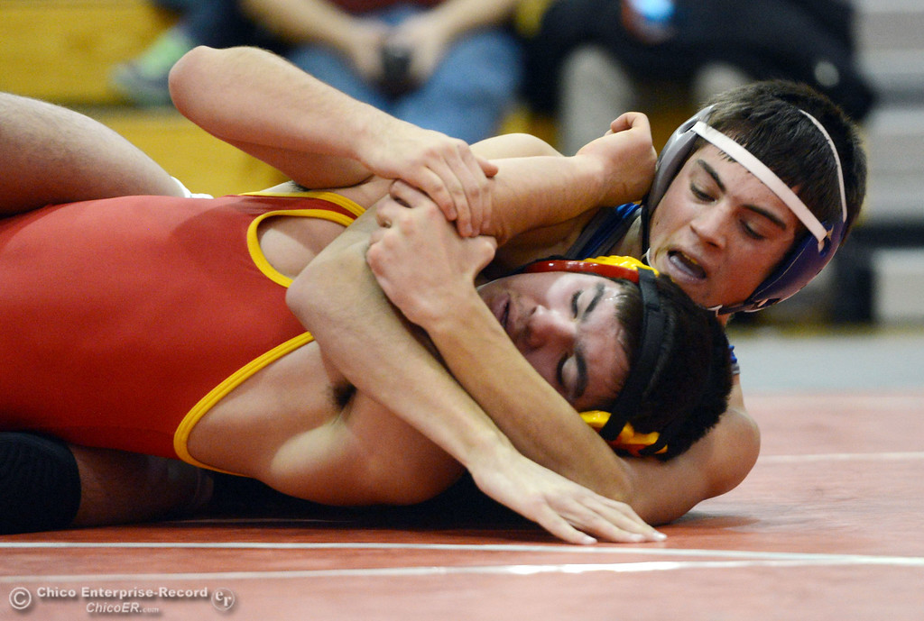 Description of . Chico High\'s Emiliano Chavez (front) wrestles against Orland High\'s Steven Abbott (back) in the 152 lbs wrestling match at CHS Wednesday, December 18, 2013 in Chico, Calif. (Jason Halley/Chico Enterprise-Record)
