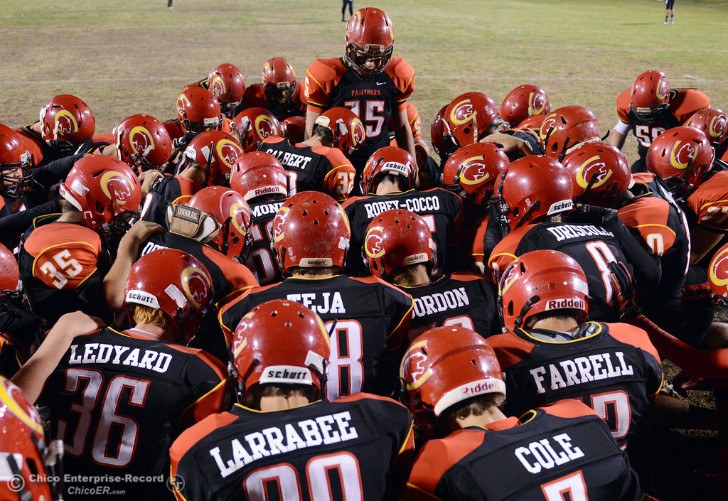 . Chico High\'s #15 Miles Fishback (top) leads the team in a prayer against Central Valley High before the first quarter of their football game at Asgard Yard Friday, September 27, 2013, in Chico, Calif.  (Jason Halley/Chico Enterprise-Record)