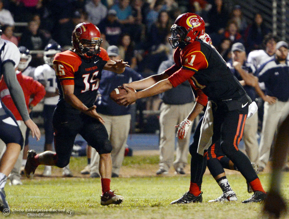 . Chico High\'s #11 Clayton Welch (right) hands off to #15 Miles Fishback (left) against Central Valley High in the first quarter of their football game at Asgard Yard Friday, September 27, 2013, in Chico, Calif.  (Jason Halley/Chico Enterprise-Record)