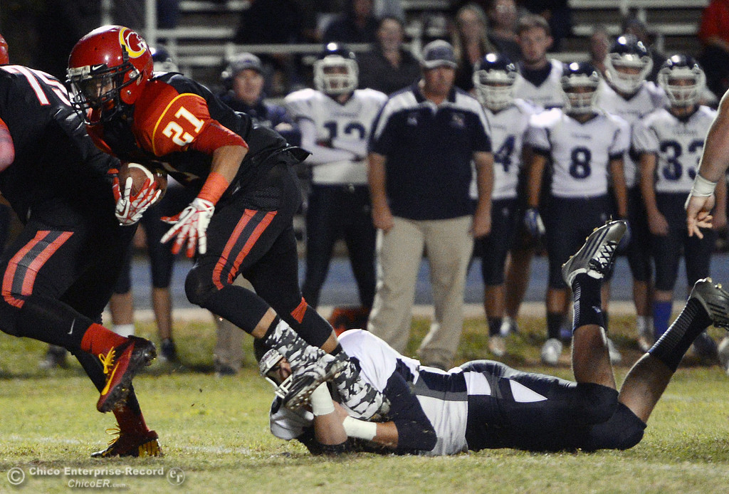 . Chico High\'s #21 Cameron Alfaro (center) breaks a tackle against Central Valley High\'s #5 Kolton Naylor (bottom) in the first quarter of their football game at Asgard Yard Friday, September 27, 2013, in Chico, Calif.  (Jason Halley/Chico Enterprise-Record)
