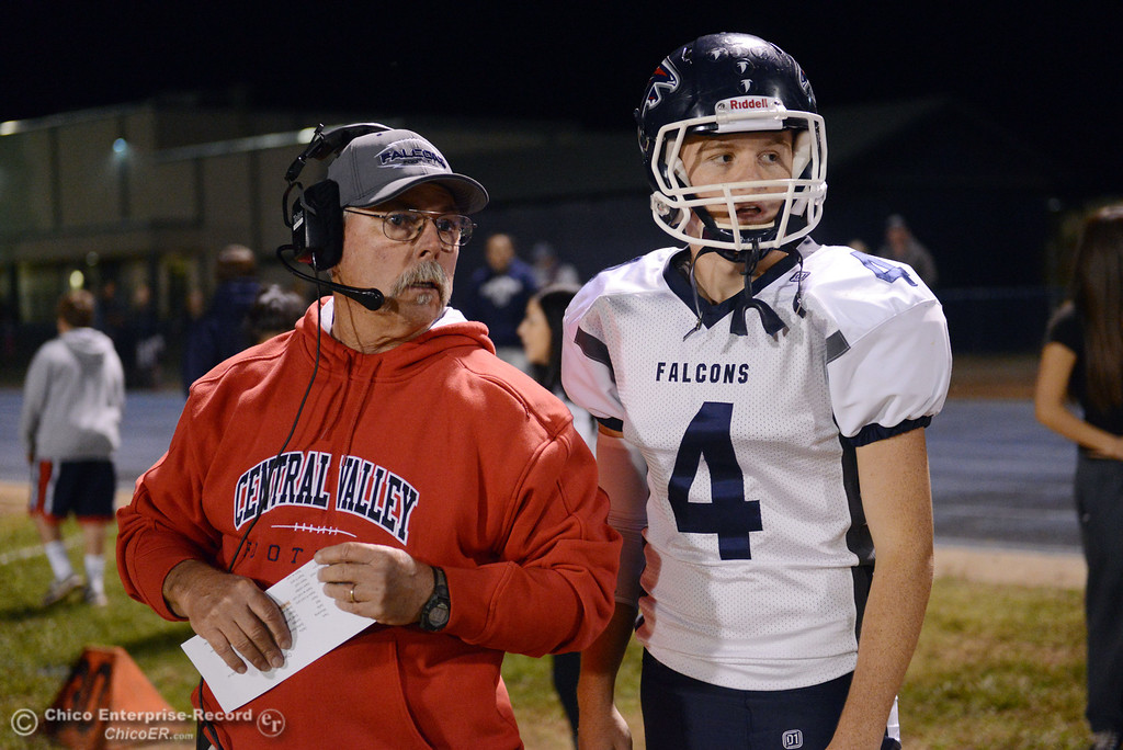. Central Valley High Coach Matt Hunsaker (left) talks to #4 Timmy Naylor (right) against Chico High in the first quarter of their football game at Asgard Yard Friday, September 27, 2013, in Chico, Calif.  (Jason Halley/Chico Enterprise-Record)