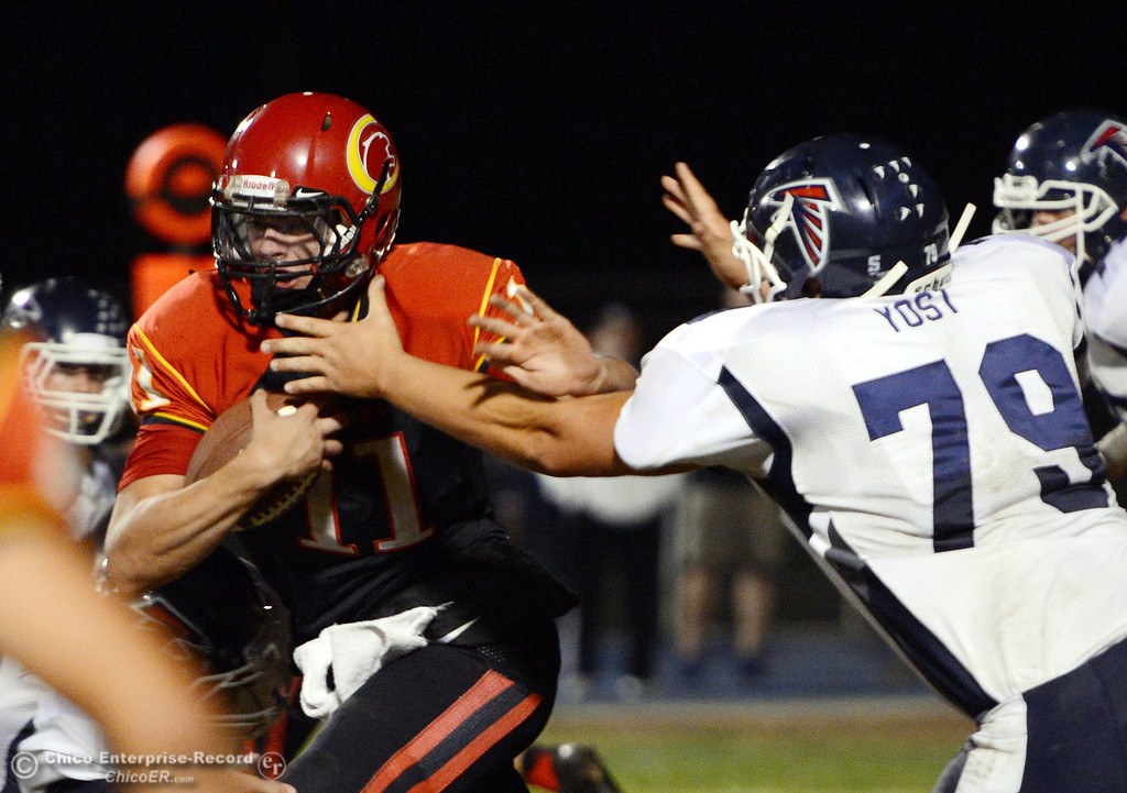 . Chico High\'s #11 Clayton Welch (left) breaks a tackle against Central Valley High\'s #79 Robert Yost (right) in the first quarter of their football game at Asgard Yard Friday, September 27, 2013, in Chico, Calif.  (Jason Halley/Chico Enterprise-Record)