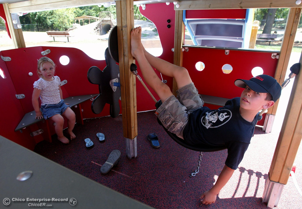 . Grace Stearns, 3 (left) and Tyler Stearns, 9 (right) lounge under the ship to beat the heat as kids play at the Nico Cardoza Memorial Park, which is now open in Caper Acres in this file photo from July 2007. (Jason Halley/Chico Enterprise-Record)