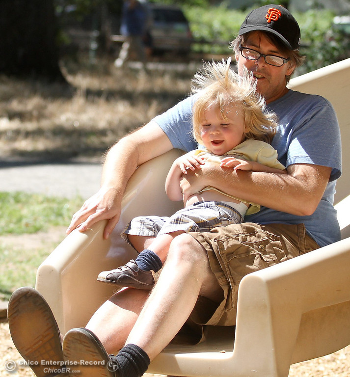 . Conrad Nystrom, of Chico, takes a ride down the slide with 1-year-old Sam Nystrom as they celebrate Fathers Day with his sons Sam and Roman 3, at Caper Acres in lower Bidwell Park in this file photo from June  2011. (Bill Husa/Chico Enterprise-Record)