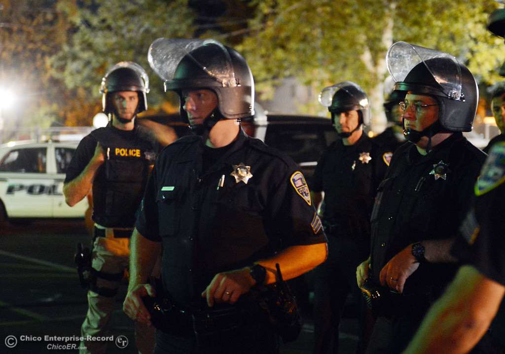 . Chico Police officers regrouped at the Notre Dame School parking lot to determine their response to large incidents in the south campus area Friday, August 23, 2013 in Chico, Calif. Police put on helmets after bottles were thrown at them.