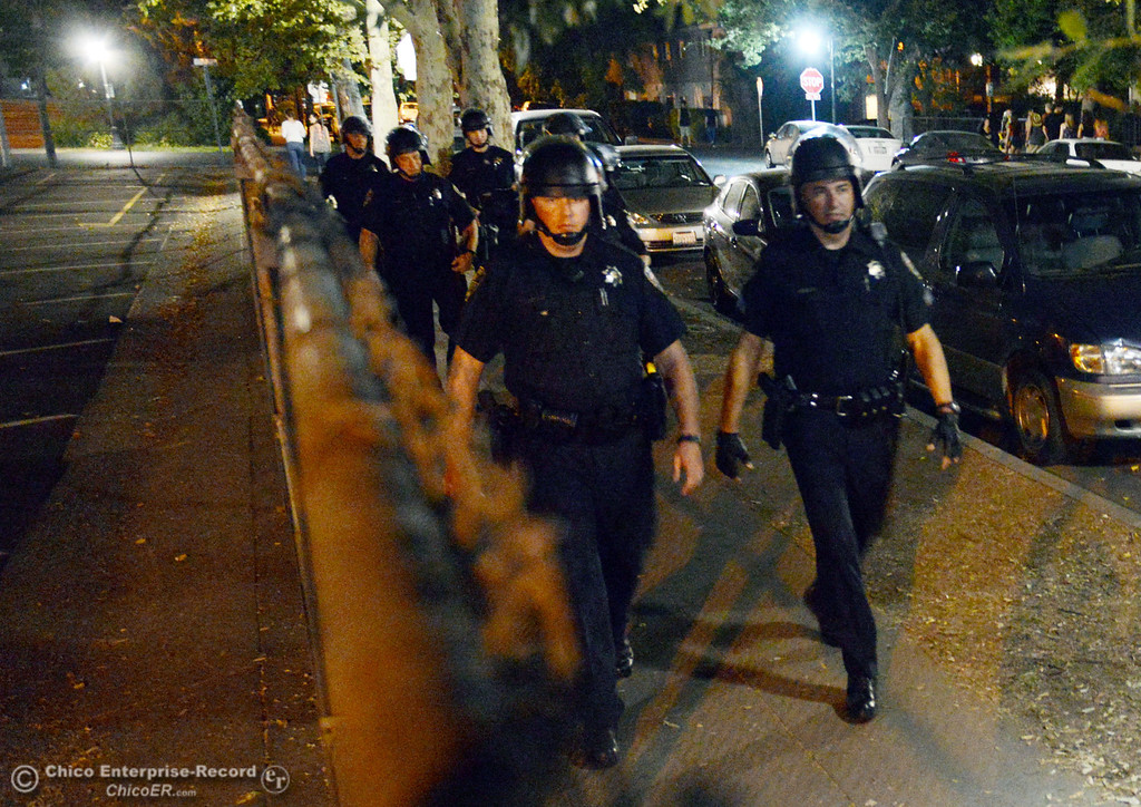 . Chico Police officer Peter Durfee (left) and Sgt. Curtis Prosise (right) lead a group from the Notre Dame School parking lot to respond to large incidents in the south campus area Friday, August 23, 2013 in Chico, Calif. Police put on helmets after bottles were thrown at them.