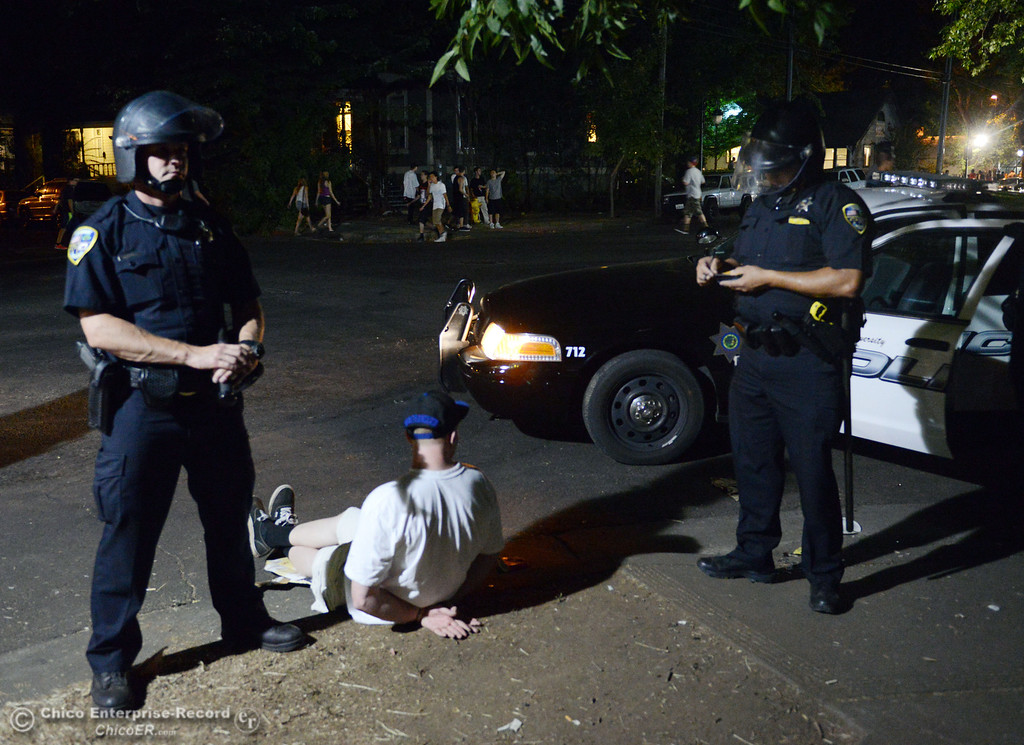 . Chico Police arrest a man after they cleared a large gathering of people at W. 6th St. and Ivy St. after trying to get to a victim of a fight in the south campus area Friday, August 23, 2013 in Chico, Calif.  Police put on helmets after bottles were thrown at them.