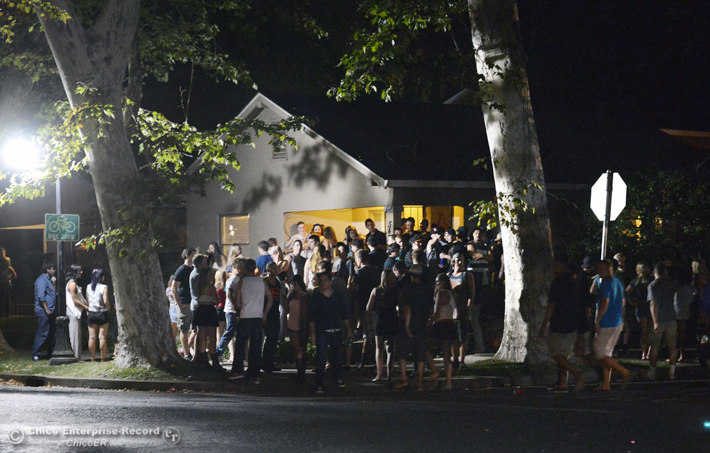 . People gather at a house on the corner of 6th St. and Ivy St. as Chico Police responded to large incidents in the south campus area Friday, August 23, 2013 in Chico, Calif. 