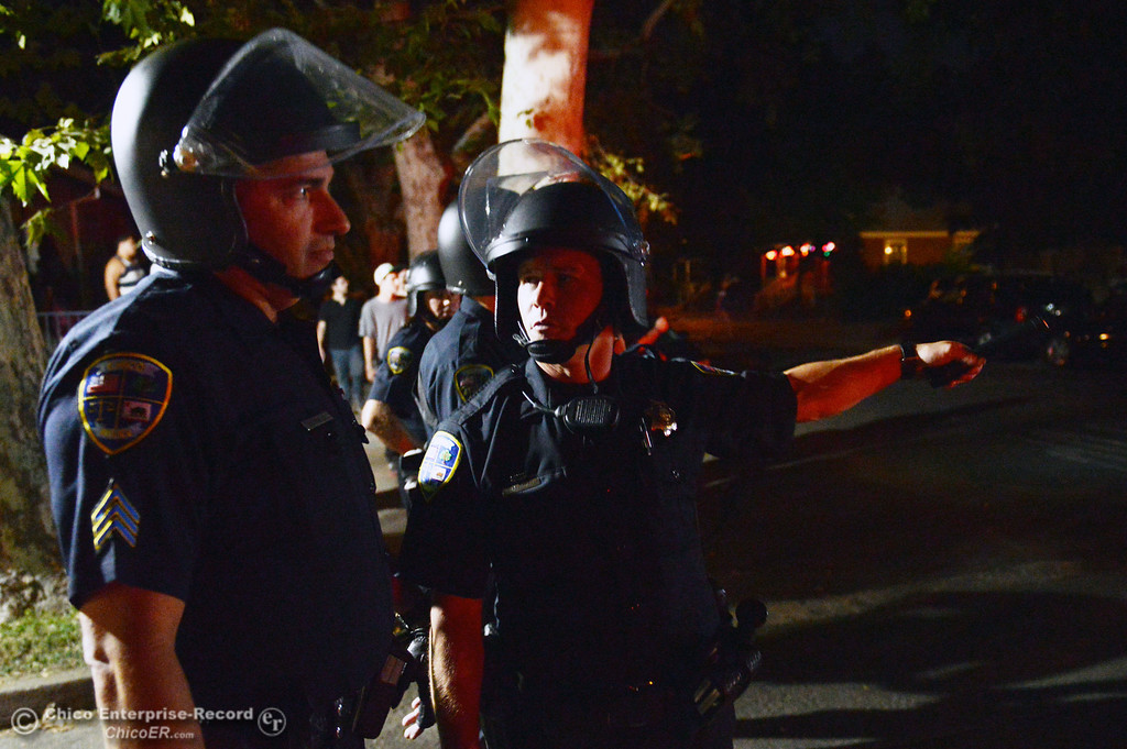 . Chico Police Sgt. Curtis Prosise (left) and officer Mike Caldwell (right) discuss what to do as they respond to a large gathering of people at W. 6th St. and Ivy St. in the south campus area Friday, August 23, 2013 in Chico, Calif.  Police put on helmets after bottles were thrown at them.