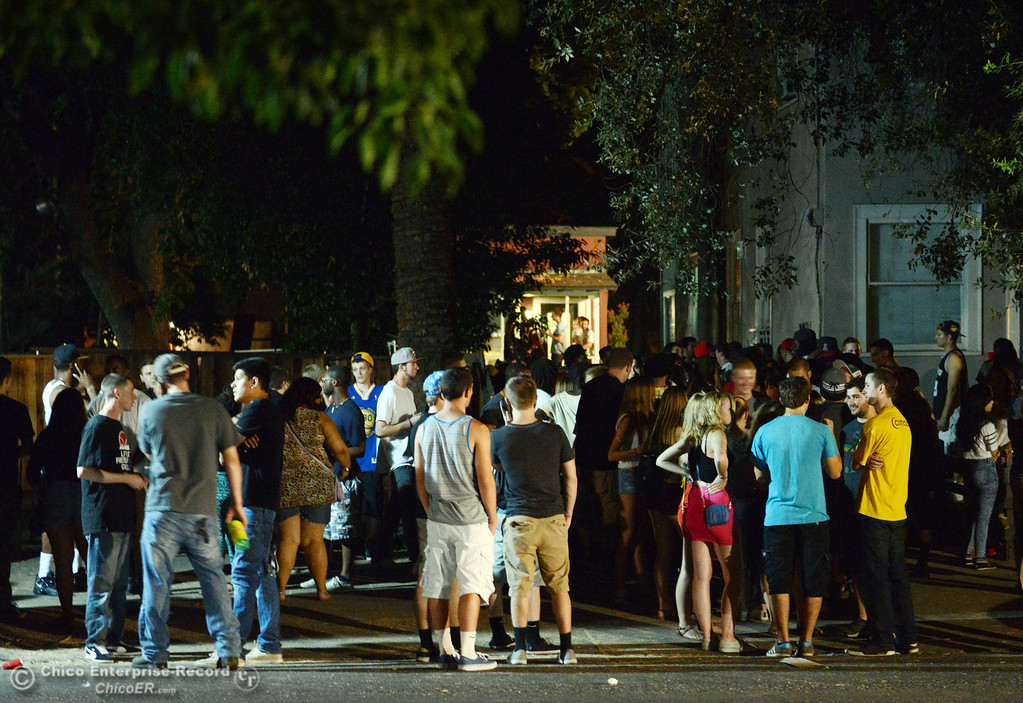 . People gather at a house along 5th St. near Ivy St. as Chico Police responded to large incidents in the south campus area Friday, August 23, 2013 in Chico, Calif. 