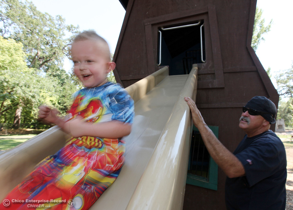 . Michael York, 3, (left) zips down a slide as Douglas York (right) plays at Caper Acres in this file photo from July 2013 in Chico, Calif. The city\'s budget is going to be closing the park on Monday through Thursday. (Jason Halley/Chico Enterprise-Record)
