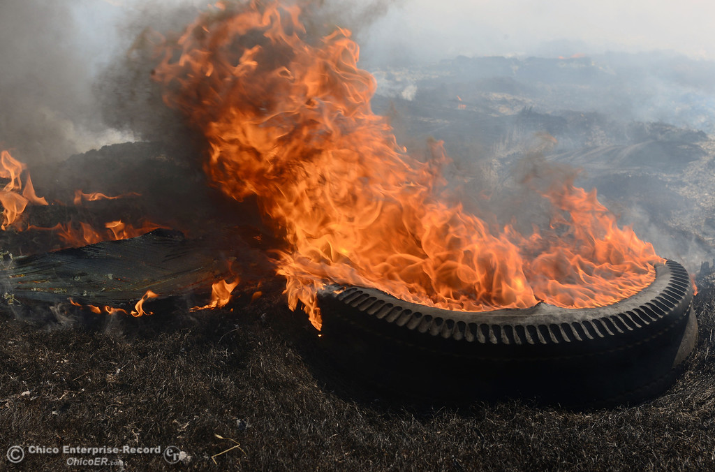 . A tire burns as Oroville Fire, El Medio Fire, and Cal Fire - Butte County battle a fire along Power House Hill Rd and Dad Lane that burned several structures and debris piles Thursday, September 26, 2013, in Oroville, Calif.  (Jason Halley/Chico Enterprise-Record)