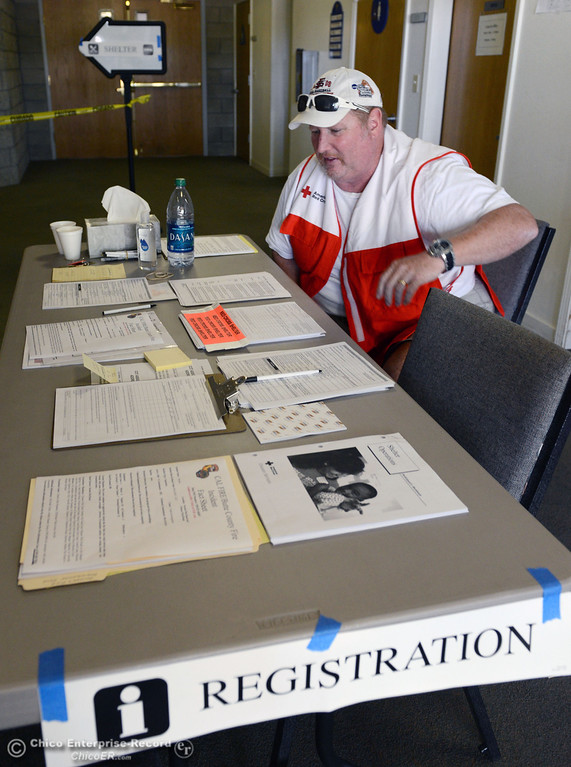 . Red Cross volunteer Chris Surber awaits people to register at the evacuation center was set up at Church of the Nazarene for mandatory evacuation areas around the Swedes Fire southeast of Oroville that were expanded just after noon Saturday, August 17, 2013 in Oroville, Calif.  (Jason Halley/Chico Enterprise-Record)