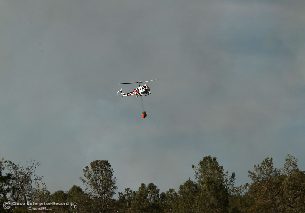 . A Cal Fire helicopter goes in to make a water drop on the Swedes Fire that burned along Swedes Flat Road, in the vicinity of Chinese Wall Road, just east or Oro Bangor Highway Friday, August 16, 2013 in Oroville, Calif. Over 200 acres were burned with at least one structure lost. (Jason Halley/Chico Enterprise-Record)