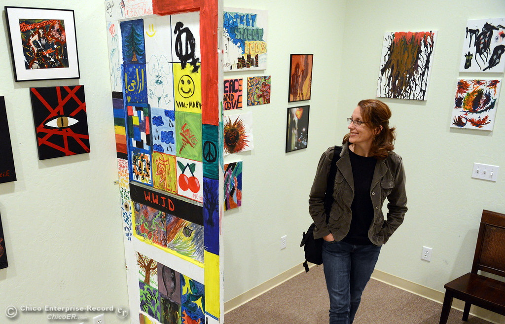 . Terri Stemen (right) looks at the art that is displayed on walls of The 6th Street Center for Youth, which hosted an open house, art show and poetry reading in recognition of Runaway and Homeless Youth Month Thursday, November 14, 2013 in Chico, Calif.  (Jason Halley/Chico Enterprise-Record)