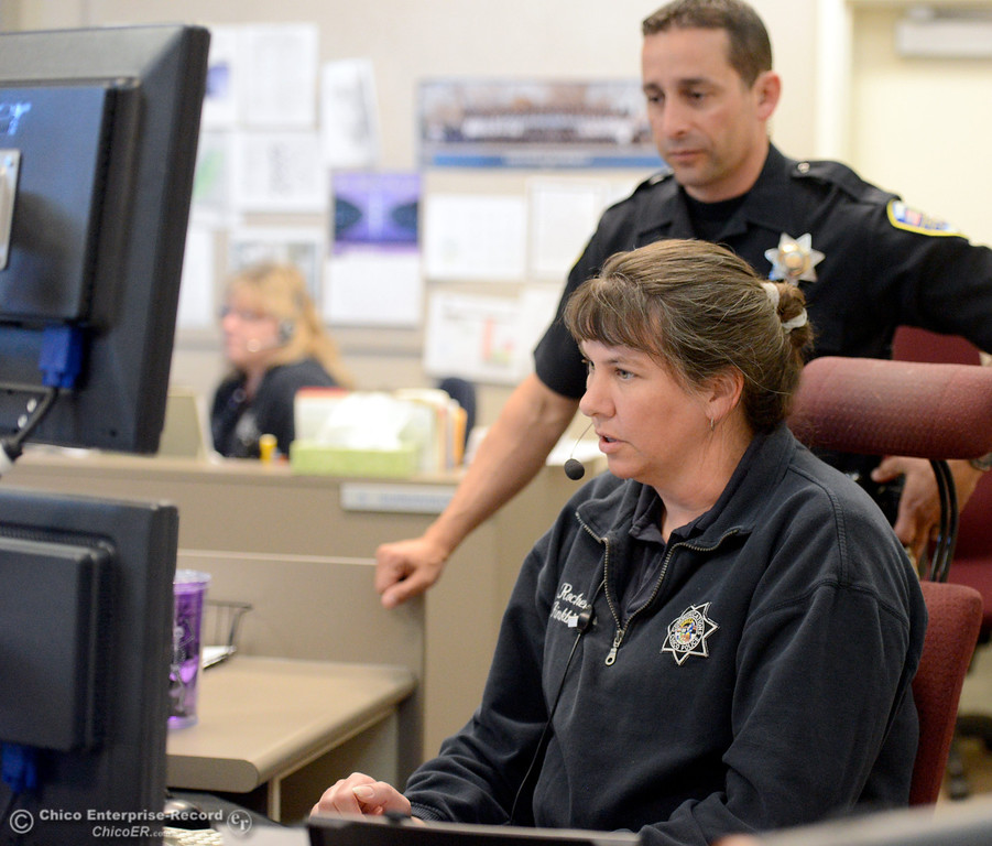 . Chico Police Officer Todd Lefkowitz looks over her shoulder as Public Safety dispatcher Rochelle Finkbiner, works in the Chico Police and Fire Dispatch Center located at the Chico Police Dept. in Chico, Calif. Wed. April 16, 2014. Being a dispatcher is a stressful job. They\'re the people who take all of the 911 calls, coordinate assistance to people who call, keep the officers safe and oversee how the Cico Police Department operates. (Bill Husa - Enterprise-Record)