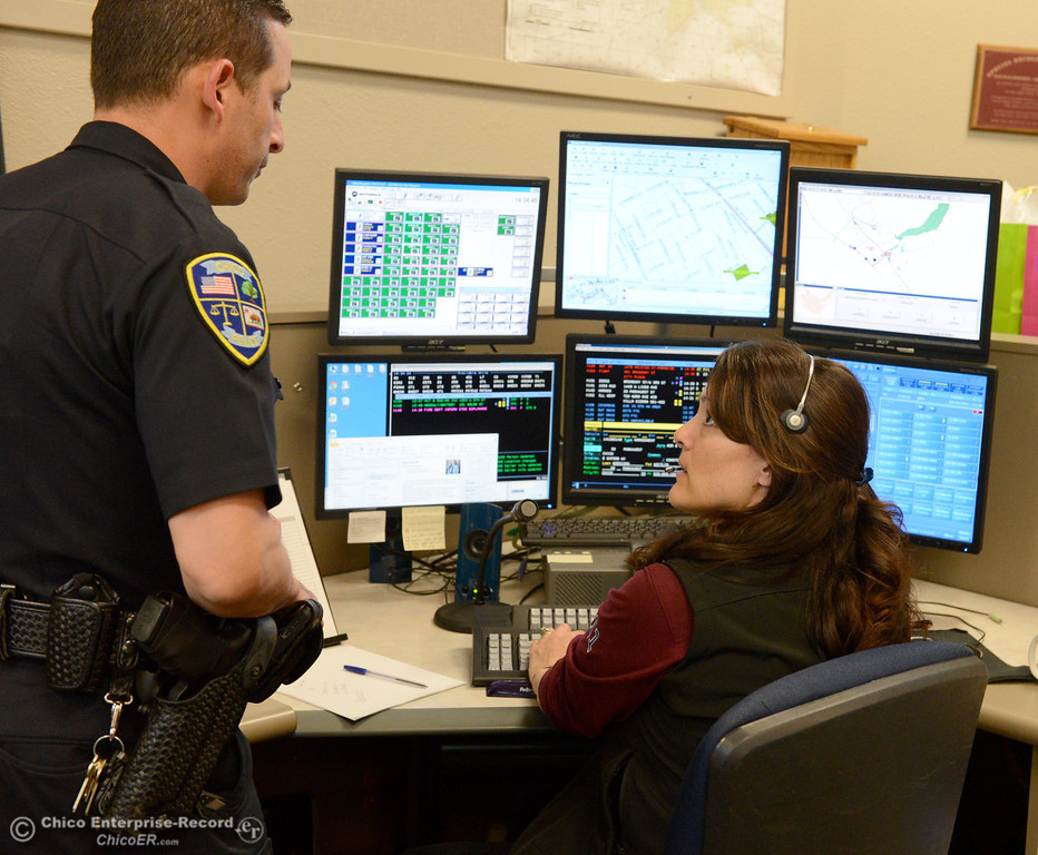 . Chico Police Officer Todd Lefkowitz talks with Public Safety dispatcher Denise Dominguez,  as she works in the Chico Police and Fire Dispatch Center located at the Chico Police Dept. in Chico, Calif. Wed. April 16, 2014. Being a dispatcher is a stressful job. They\'re the people who take all of the 911 calls, coordinate assistance to people who call, keep the officers safe and oversee how the Cico Police Department operates. (Bill Husa - Enterprise-Record)