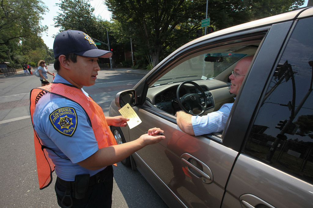 . Michael Lai, University Police Department officer, fills out a time permit for Wally Smith to be able to park on Legion Ave. so he can can off load his son\'s things into his new dorm rooms at Chico State on Tuesday, August 20, 2013. (Frank Rebelo/Staff Photo)