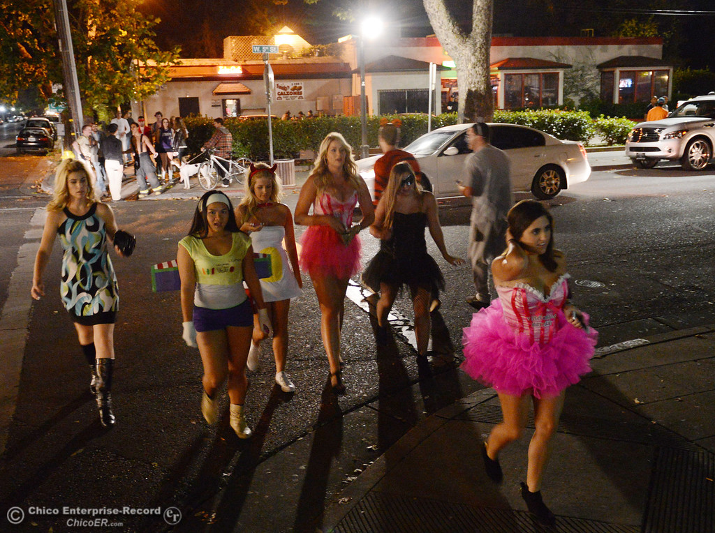 . Chico Police keep an eye on the costumed crowd that walk through the 5th Street and Ivy Street in downtown and south Chico State campus area for Halloween Thursday, October 31, 2013 in Chico, Calif.  (Jason Halley/Chico Enterprise-Record)